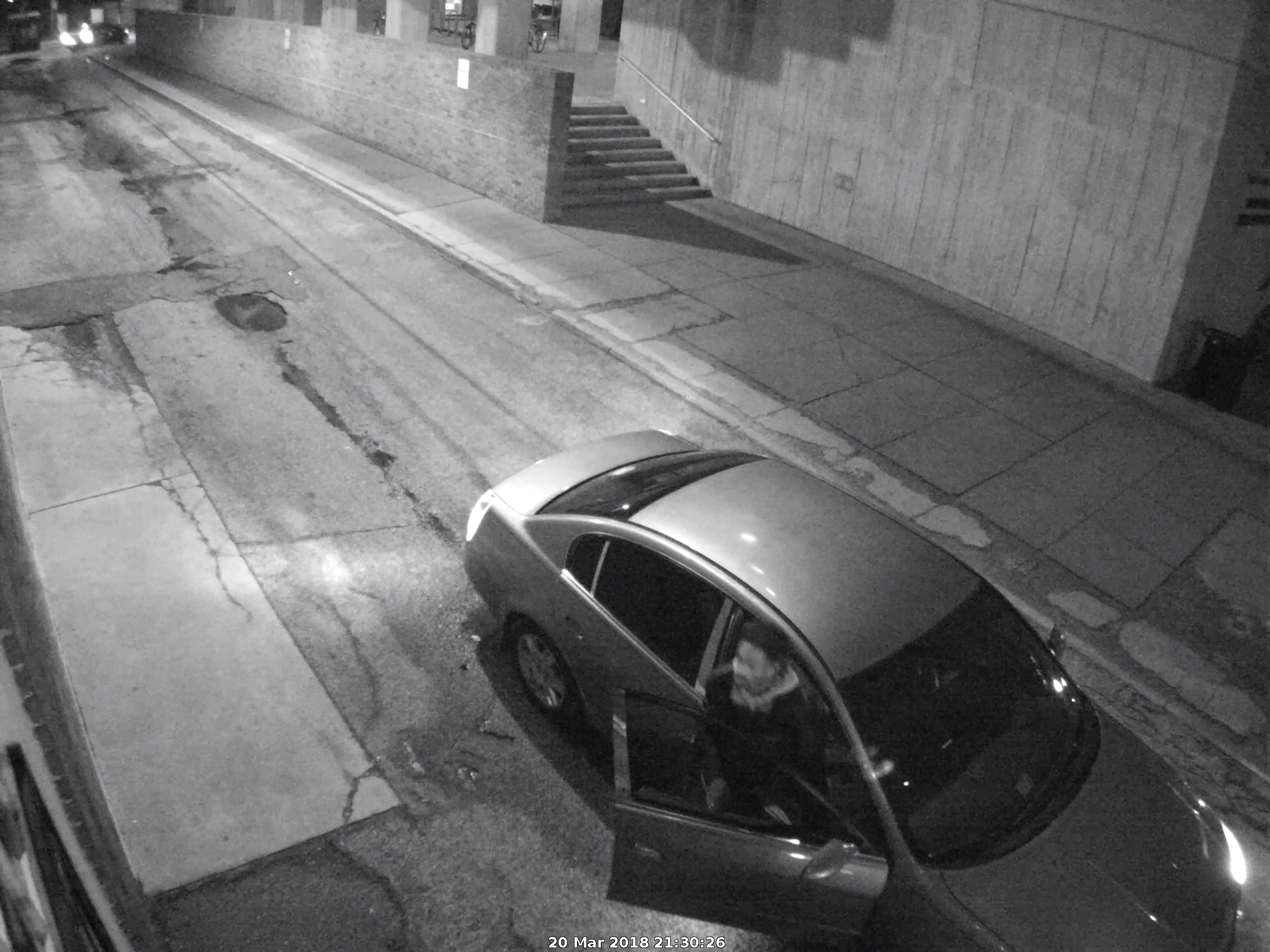 Image Description: A man exits the passenger side of a grey or silver Nissan Altima that's parked in an alley near Harrison Street; police believe the vehicle is a 2005 or 2008 model. (VCU Police suspect photo.)