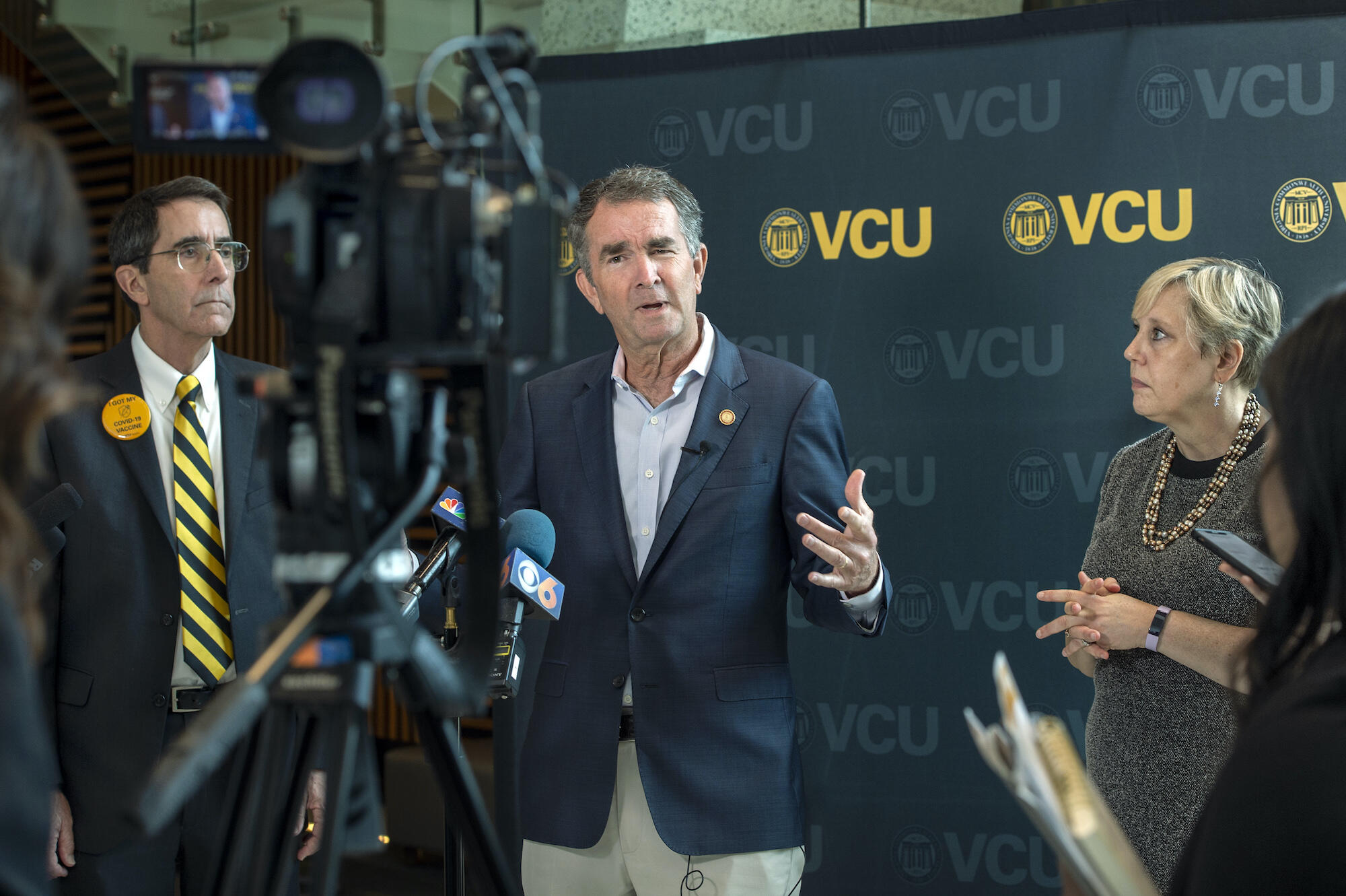 Virginia Gov. Ralph Northam, M.D., (center) addresses reporters Thursday as Art Kellermann, M.D., (left) senior vice president for VCU Health Sciences and CEO of VCU Health System, and Susan Parish, Ph.D., (right) dean of VCU's College of Health Professions, look on during the governor's visit to the college's building.