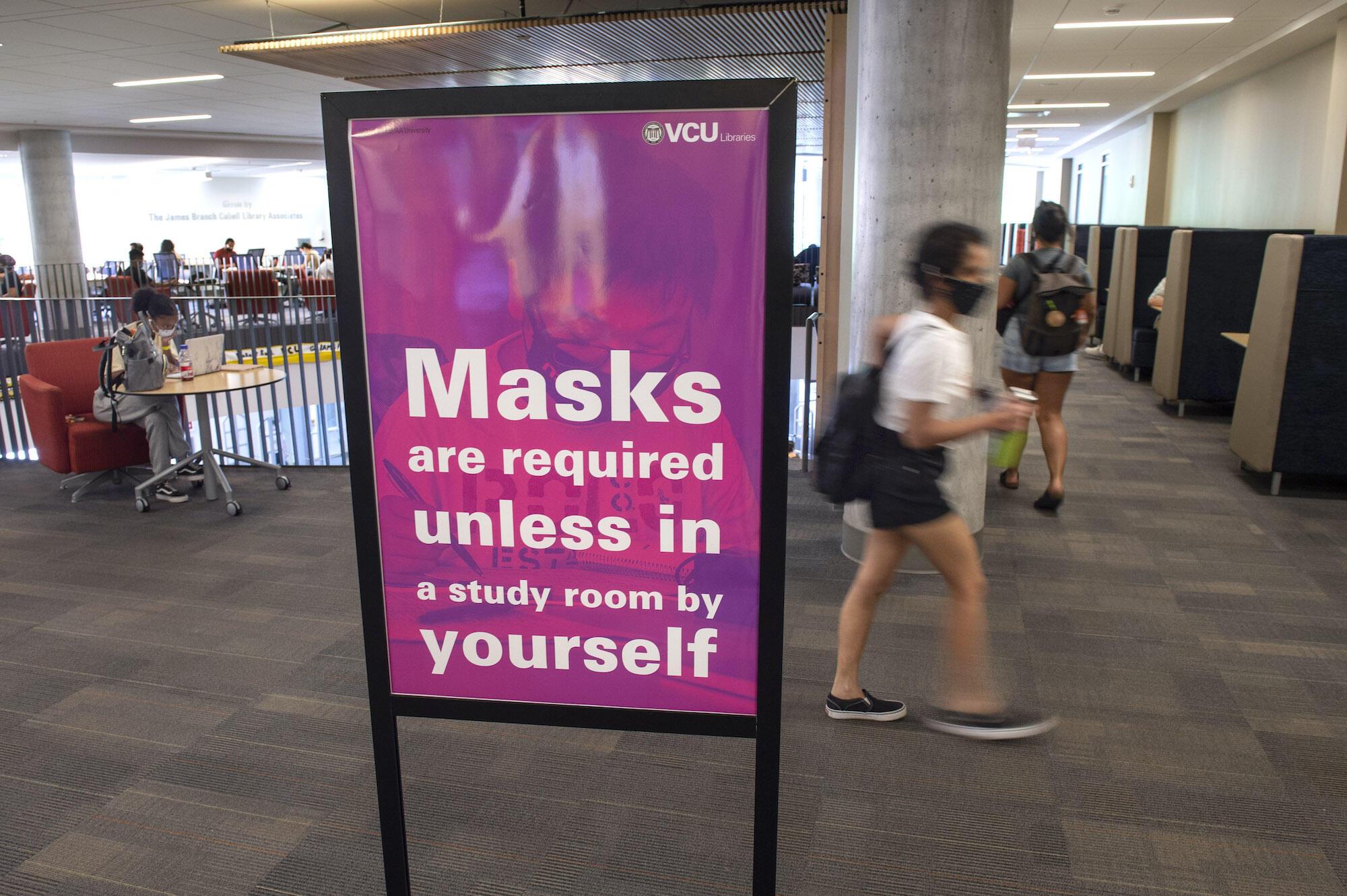 Um sinal que descreve os requisitos de máscara na biblioteca Cabell.