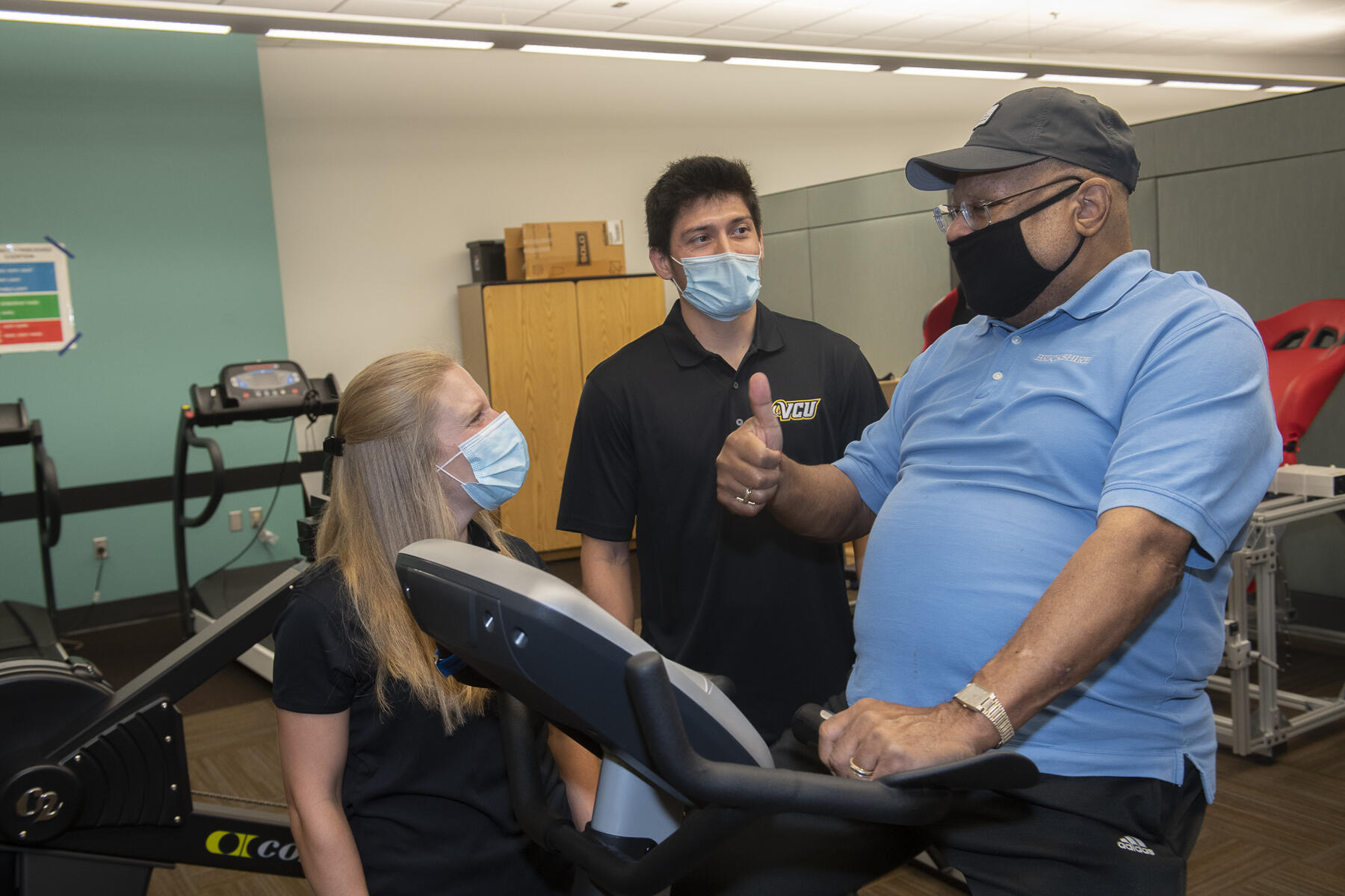 an older man gives a thumbs up to two trainers as he pedals on an exercise bike
